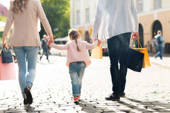 Close up of family with child shopping in city. Sale, consumerism and people concept - close up of happy family with little child and shopping bags in city Royalty Free Stock Photo