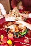 Close-up family clinking glasses on Thanksgiving on a table background. Cheers with champagne. Celebration concept. stock images