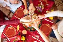 Close-up family clinking glasses on Thanksgiving on a table background. Cheers with champagne. Celebration concept. stock photos
