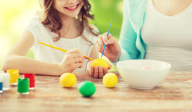Close up of family coloring easter eggs. Easter, family, holiday, people and childhood concept - close up of happy girl and mother with brushes coloring easter Stock Photo