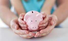 Close up of family hands with piggy bank Royalty Free Stock Photo