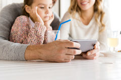 Close up of family with smartphone at restaurant Royalty Free Stock Photos