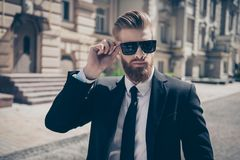 Close up of a famous guy in formal wear and sunglasses outdoors. He has very stylish bear and hairdo Royalty Free Stock Photos