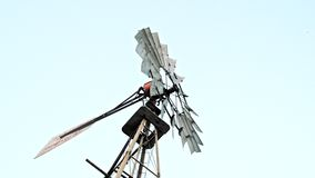 Close up of a farm windmill against skies. 4K. UHD stock video