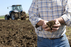 Close up of farmer cupping soil in ploughed field with tractor in background Royalty Free Stock Photos