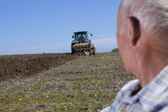 Close up of farmer watching tractor and plough in field Stock Image