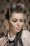 Close-up of fashion creative woman. Close-up fashion portrait of charming female with creative look, cute brunette hair-style and strong make-up. Wearing white Royalty Free Stock Photography
