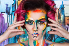 Close-up fashion faceart portrait of young girl. Close-up fashion surrealist faceart portrait of young girl with art painting posing. Amazing creative picture stock photo