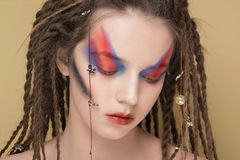 Close-Up Fashion female Model with colorful abstract makeup and dreadlocks hairstyle.  Royalty Free Stock Photos