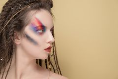 Close-Up Fashion female Model with colorful abstract makeup and dreadlocks hairstyle.  Stock Photo