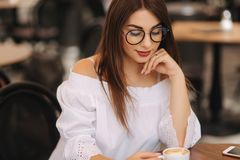 Close up fashion image of woman holding white cup of her morning cappuccino, wearing white stylish clothes and vintage royalty free stock images