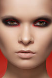 Close-up fashion model face with dark rock make-up. Close-up beauty portrait of attractive model face with bright fashion make-up. Devil style visage for Stock Images