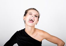 Close-up fashion photo of young lady in elegant black dress, playful woman shows tongue Stock Images