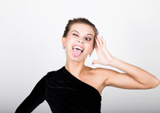 Close-up fashion photo of young lady in elegant black dress, playful woman shows tongue Royalty Free Stock Photos
