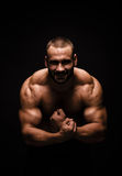 A portrait of a male with flexing muscles on a black background. Fitness training. A bodybuilder with a perfect body. Stock Photo