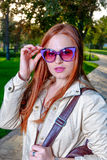 Close up fashion portrait of pretty seductive young woman with funny violet sunglasses, posing outdoor. Red lips, long Stock Photo