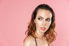 Close up fashion portrait of a pretty young woman. Wearing makeup dressed in bodysuit posing while standing  over pink background Stock Photos