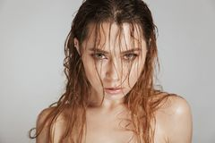Close up fashion portrait of a topless seductive woman. With makeup and wet hair posing isolated over gray background royalty free stock image