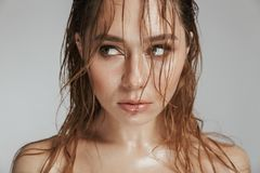 Close up fashion portrait of a topless seductive woman. With makeup and wet hair posing isolated over gray background royalty free stock images