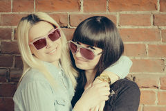 Close up fashion portrait of two girls hugs and having fun together, wearing stylish sunglasses, best fiend enjoy amazing time tog Royalty Free Stock Photography