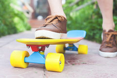 Close-up fashion skateboarder riding skateboard outdoor. Skatebord at city, street. Shoes, stylish sneakers. Longboard. Cool, Fun Tenager. Skateboarding at Stock Photo