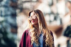 Close up fashion street stile portrait of pretty girl in fall casual outfit Beautiful blond posing outdoor. Girl wearing stylish burgundy coat and red lips Royalty Free Stock Photo