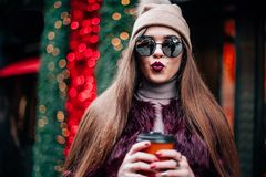 Close up fashion street stile portrait of pretty girl in fall casual outfit Beautiful brunette posing outdoor. Burgundy fur coat of artificial fur knitted hat Stock Images
