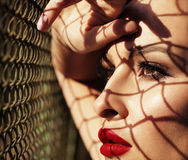 Close up fashion woman model portrait with red lips, shadows fro. M grid on face stock photography
