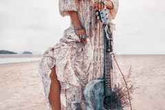 Close up of fashionable young woman legs. Fashion model with guitar outdoors at sunset royalty free stock photography