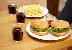 Close up of fast food and drinks on table at home Royalty Free Stock Photography