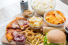 Close up of fast food snacks and drink on table Royalty Free Stock Images