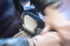 Close up of fastened airplane seat belt with dramatic zoom effect. Royalty Free Stock Image