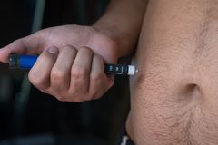 Close up of fat man hands making injection with insulin pen or s royalty free stock photography