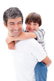 Close-up of father giving his son piggyback ride. Against a white background Royalty Free Stock Photos