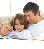 Close-up of father and his children reading book. Lying in bed with little boy looking at camera stock images