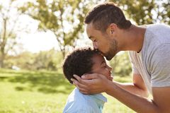 Close Up Of Father Kissing Son In Park royalty free stock image