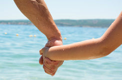 Close up of father and little daughter holding each other hands Stock Photography