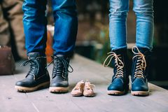 Close-up of father, mother and future little son feet in shoes royalty free stock photo