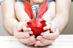 Close up of father and son hands holding piggy bank. Close up of father and son hands holding red piggy bank Royalty Free Stock Photos