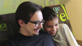 Close-up father and son are looking together in the phone and laughing. stock video footage