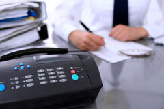 Close up of fax machine near business woman making  report, calculating or checking balance. Bookkeeper or female financial inspector  making report Stock Photo
