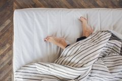 Feet of a woman sleeping on the white linen at home royalty free stock photo