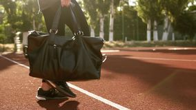 Close up of the feet in black sneakers- fit young woman is going to the stadium with the brown covering. There is a. Black sport bag in her hand and she puts it stock footage
