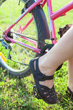 Close-up of feet of Caucasian rider sitting on the bike Royalty Free Stock Photography