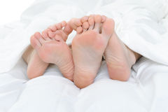 Close-up of the feet of a couple on the bed Stock Photography