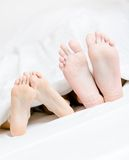 Close up of feet of the couple lying in bed Royalty Free Stock Photos