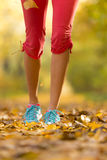 Close up of feet of female runner. Running in autumn leaves. Fitness exercise, low depth of focus royalty free stock image