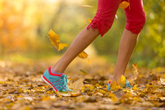 Close up of feet of female runner. Running in autumn leaves. Fitness exercise, low depth of focus royalty free stock photos