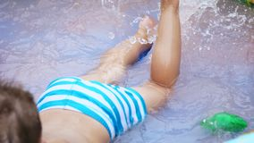 Close-up of feet. a four-year-old boy lies in a children`s inflatable pool, splashing with water, splashes scatter stock video