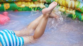 Close-up of feet. a four-year-old boy lies in a children`s inflatable pool, splashing with water, splashes scatter stock video footage